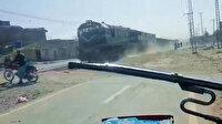 Pakistan'da motosiklet sürücüsü, trenin altında kalmaktan saniyelerle kurtuldu