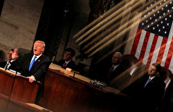 U.S. President Donald Trump and Vice President Mike Pence are seen behind the reflection of a House chamber railing as Trump delivers his State of the Union address to a joint session of the U.S. Congress on Capitol Hill in Washington, U.S., January 30, 2018.