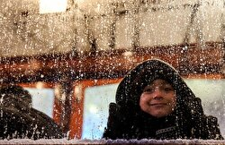 A child smiles while looking out at the snow.