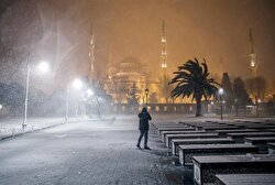 A woman is seen outside of the almost deserted Sultanahmet Mosque.