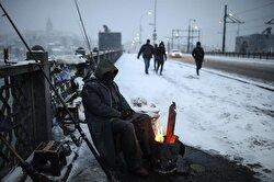 A fisherman on Galata Bridge sits by the fire to keep warm.