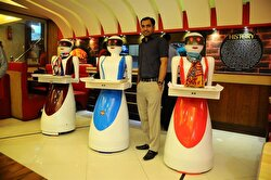 Osama Aziz poses for a photo with robot waitresses, which are built and developed by himself, at a local fast food restaurant in Multan, Pakistan on July 08, 2017.