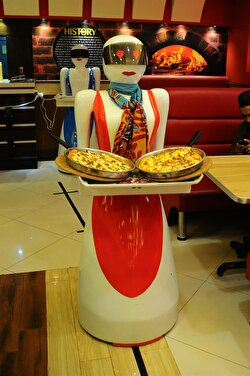 A robot waitress, which is built and developed by restaurant's owner's electrical engineer son Osama Aziz, services meal at a local fast food restaurant in Multan, Pakistan on July 08, 2017.