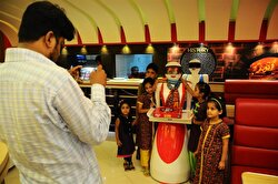 People pose for a photo with a robot waitress, which is built and developed by restaurant's owner's electrical engineer son Osama Aziz, at a local fast food restaurant in Multan, Pakistan on July 08, 2017.
