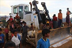 Rohingya kids, fled from ongoing military operations in Myanmar's Rakhine state, play around a heavy construction machine, parked for a road construction inside a makeshift refugee camp in Balukhali in Cox's Bazar, Bangladesh on October 09, 2017.