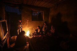 A Palestinian Abu Shavish family members try to warm themselves around a fire inside their house without a door and windows as they live in hard conditions on a cold day in Zeitoun district of Gaza City, Gaza on January 05, 2018.