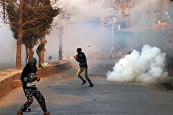 A Kashmiri protester dodges as a stun grenade explodes in old city Srinagar the summer capital of Indian controlled Kashmir on January 13, 2018. Government imposed restrictions in many parts of Srinagar to foil pro freedom protest called by Kashmiri separatists leaders against the killing of civilians by Indian forces during anti insurgency operations.