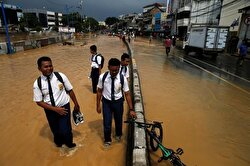 Students on their way to school wade through a flooded street in Jakarta