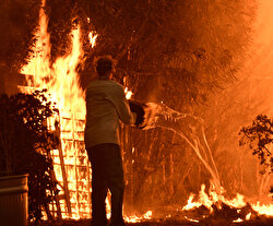 Wildfires burned out of control on Friday across California, killing at least nine people in a mountain town and forcing residents to flee the upscale beach community of Malibu in the face of a monster fire storm.