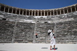Tourists take photos at antique theatre of Aspendos, built by the Romans in 160-180 A.D, in Serik district of Antalya, Turkey on August 6, 2019. Aspendos, which is among the examples of the best designed Roman theaters, is one of the best-preserved ancient amphitheater and is still used for concerts and festivals.
