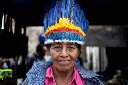 An indigenous woman of Colombian Amazon poses for a photo as she visits a market for cultural exchange in Bogota, Colombia on August 20, 2019.