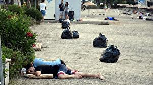 Sahilde uyuyan tatilcilerin arasında torbalar dolusu çöp topladılar