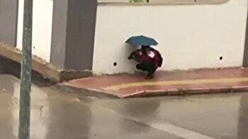 جلس لدقائق يحمي كلبًا من الأمطار الغزيرة في أنطاليا التركية