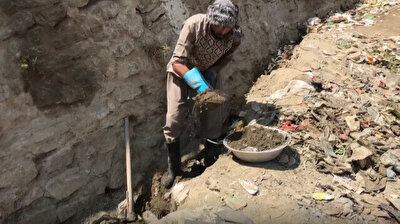 Afghan man digs river bed in search of gold for family's survival