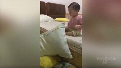 Careful baby uses pillows to get down from bed