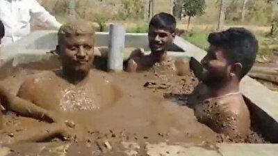 Indian men take cow dung bath to keep coronavirus away