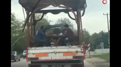 Turks play backgammon on picnic table at the back of moving truck