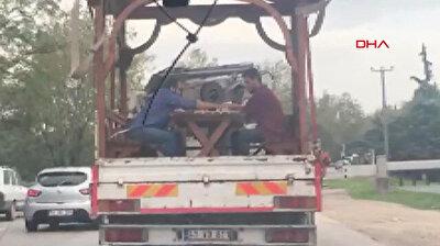 شاهد.. شخصان يستمتعان بلعب الطاولة على متن شاحنة تسير