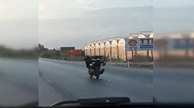رحلة محفوفة بالمخاطر.. يقود دراجته النارية وهو مستلقٍ دون اكتراث
