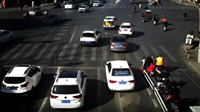Terrifying footage shows the heartstopping moment a four-year-old boy suddenly fell from the back of a moving vehicle amid busy traffic in China's Fuyang city, as the kid wandered off at the busy intersection much to the shock of commuters and onlookers.