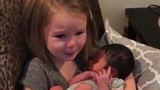 Kucağına bebek alınca gözyaşlarını tutamayan güzel kalpli küçük kız