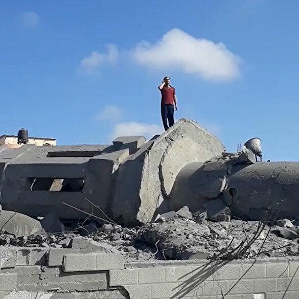 Filistinli adam işgalci İsrail'in Gazze'de yerle bir ettiği caminin enkazına çıkıp ezan okudu