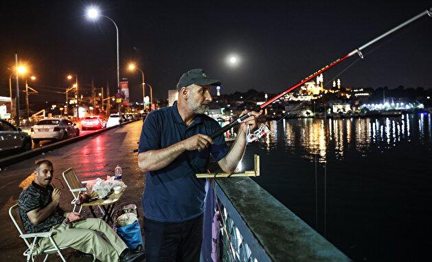 Fishermen catch fish at Galata Bridge in Istanbul