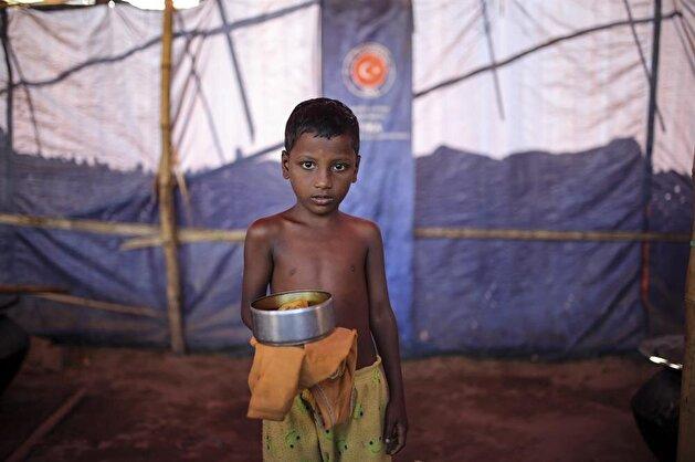 Rohingya children help distribute food aid at refugee camp