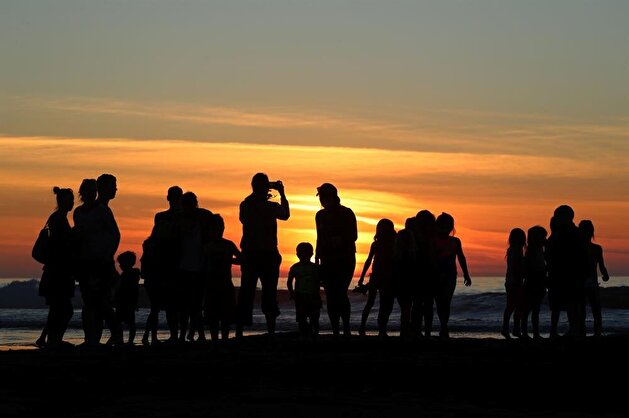Californians enjoy sunset during low tide
