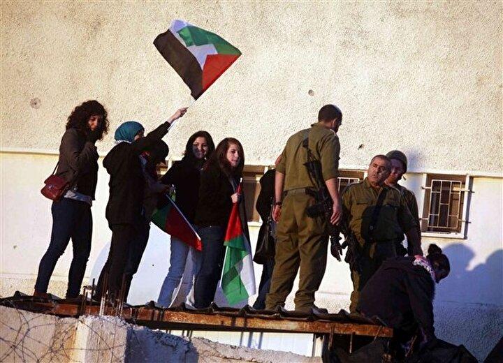 Ramallahta bir grup Filistinli kadın, Filistin bayrakları ve sarsılmadan seninleyiz yazan pankartlarla İsrail askeri kampına girdiler.