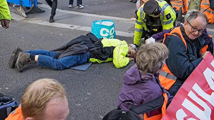 İngilterede ilginç protesto: Çevreciler yüzünü yapıştırıcıyla asfalta yapıştırdı