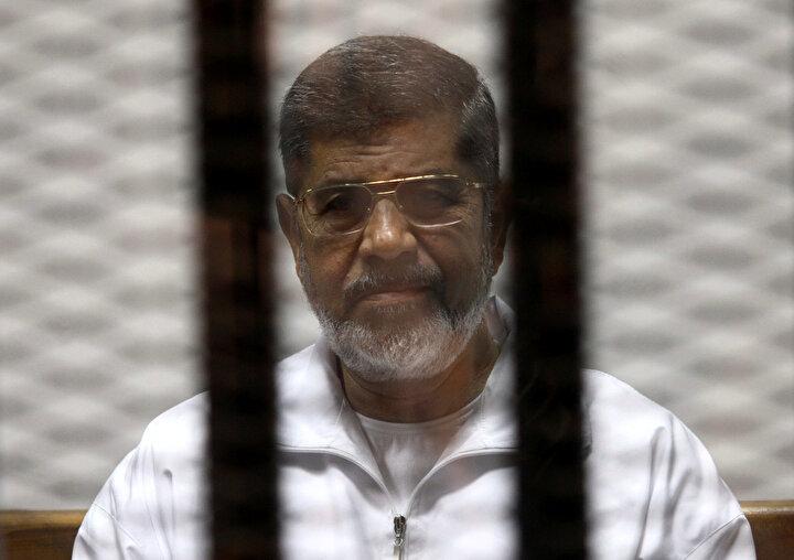 Cumhurbaşkanı Mursi Ocak 2014'te, 21 sanıkla birlikte yargılandığı hapishane baskınları davasının duruşmasında ilk defa mahkumların zorunlu olarak giydiği beyaz elbiseyle görüldü.