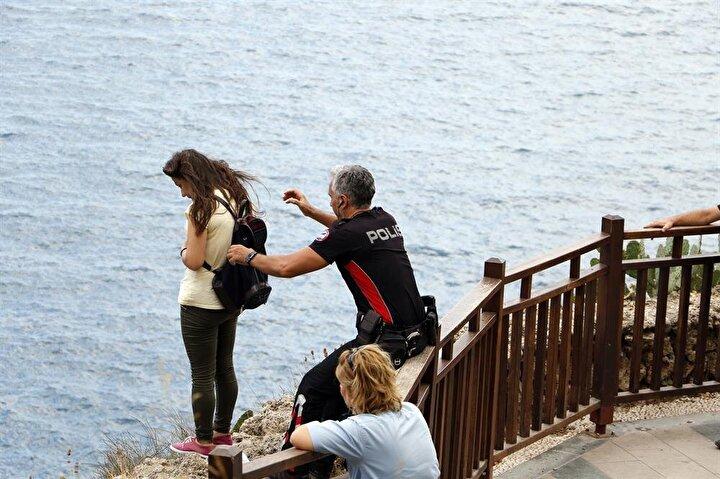 Polis memuru, daha sonra genç kadını sol koluyla sarıp kendine doğru çekti.