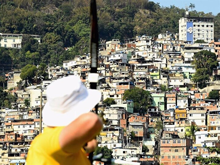 Avustralyalı bir okçu Rio şehrinin kenar mahallelerine karşı nişan alıyor.