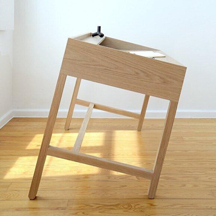 Devrilmek üzereymiş gibi duran bir aslında asimetrik tasarıma sahip olan çalışma masası.