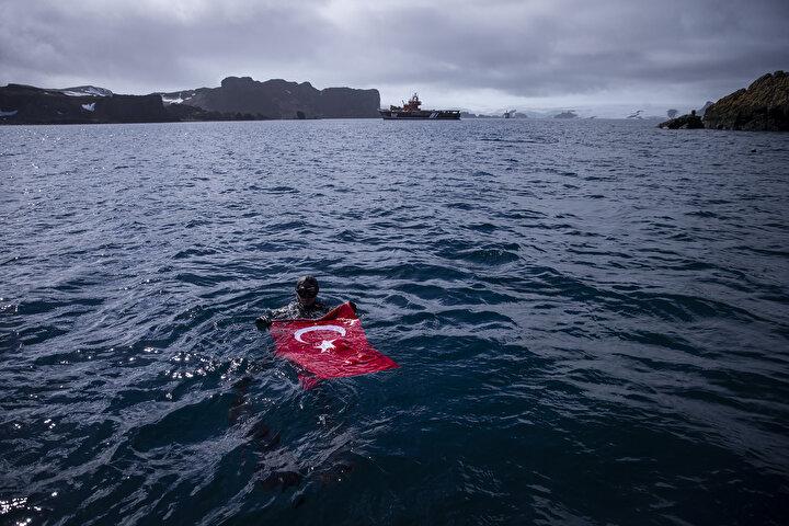 Antarktikadayız, bunu bilerek daldık ama gerçekten insan şartlarını zorlayan bir soğukluk var. Burada dalış yapmak bizim için de bir ilk. Sembolik de olsa bilim çalışmasının bir parçası olarak Antarktikada bayrağımızı dalgalandırmak soğuğu ve acıyı unutturuyor, öyle müthiş bir gurur var içimizde.