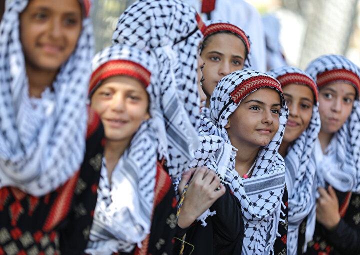Filistinin geleneksel el sanatlarından olan kanaviçe işli elbiselerini giyen kadınlar ile kefiyelerini takan adamlar, dedelerinin, göç ettirildikleri 1948 topraklarında çekilmiş fotoğraflarını taşıdı.