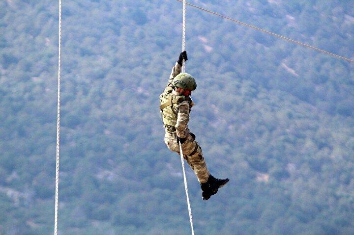 Yine helikopter içerisinde mavi berelilere öğretmenleri tarafından uzun menzilli silahlarla atış eğitimi veriliyor.