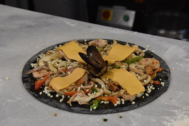 Siyah hamurlu pizzayı da müşterilerimizin beğeneceğini düşünerek menümüze koyduk. Gelen yorumlar da çok olumlu. Pizzanın içinde tamamen deniz ürünleri var. Hamura renk veren sübyenin yanı sıra; karides, iç midye, somon ve biber çeşitlerini kullanıyoruz. İlk zamanlarda müşteriler şaşırıyordu. Fakat zamanla beğendiler.