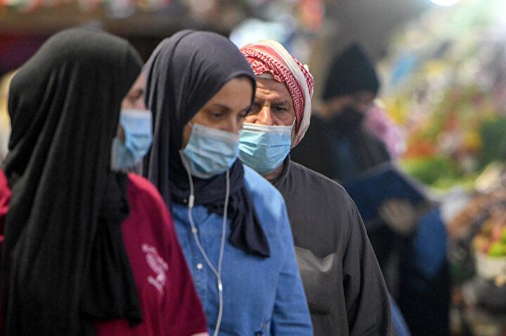 Kuveyt'te maske ile önlem alan insanlar.