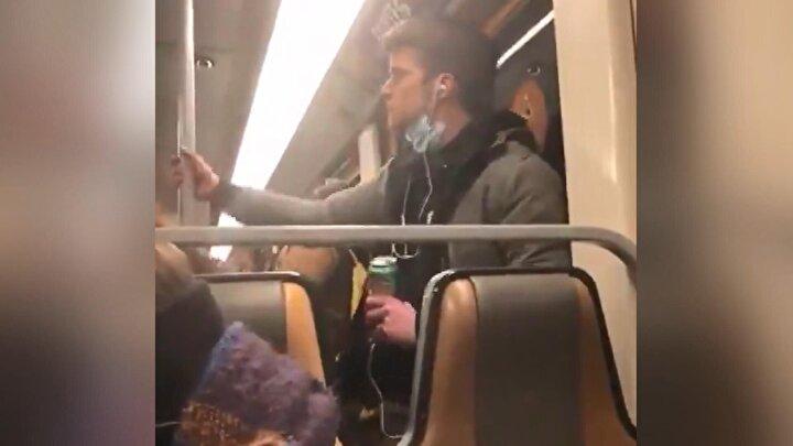 Belçikanın başkenti Brükselde metroya binen maskeli adam, yüzündeki maskeyi aşağıya çekerek parmaklarını ağzına götürdü.