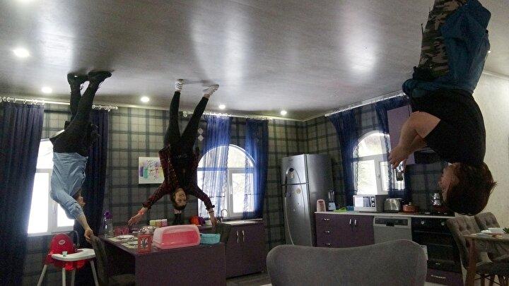 Dubleks evin tamamen ters çevrilerek, eşyaların tavana yerleştirildiği binaya girenler, tavanda yürüdükleri hissine kapılıyor.