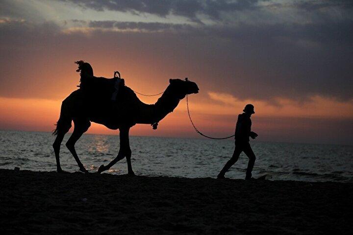 Gazze kentinde bazı Filistinliler, gün batımı eşliğinde sahilde vakit geçirdi.