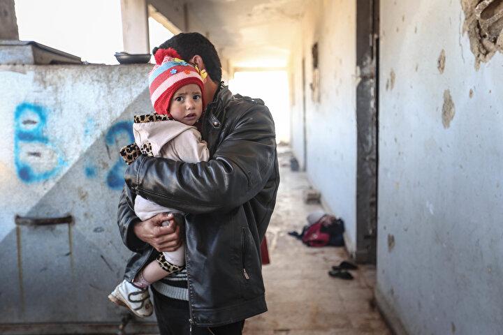 Maarratunnüman ilçesinden 2 yetim torunu ve kocası ile göç etmek zorunda kalan 70 yaşındaki Adile Rahmun, başını sokacak bir yer bulamayınca 16 aile ile birlikte büyük kısmı hasar gören yan yana iki okula sığındı.