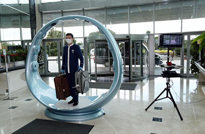 DEZENFEKTAN TÜNELİ VE TERMAL KAMERA  Otelde hazırlanan senaryoya göre, bir müşterinin havalimanından otele gelişi ve tatil süreciyle ilgili uygulamalı test yapıldı. Havalimanına iniş yapan turist, dezenfektan işlemi yapılan araçlarla otele getiriliyor. Otel girişinde turistlerin ateşi ölçülüyor. Müşteri araçtan indikten sonra, araç ve bavulları yeniden dezenfekte ediliyor. Otelin ana giriş kapısında ise termal kamera ile ateşleri ölçülüyor ve ayrıca dezenfektan tüneline giriyor.