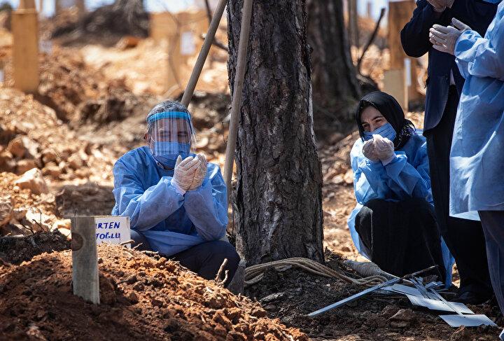 Defin törenine gelen bir grup cenaze yakınının ise virüs salgınına karşı koruyucu tulum, maske ve siperlik taktığı görüldü.