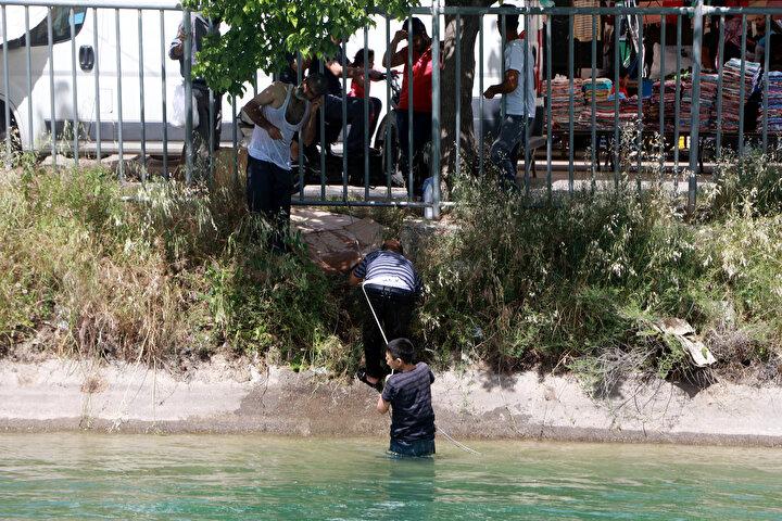 """Kanalda yüzen gençlerden biri, Havalar çok sıcak, yanıyoruz. Havuzlar kapalı olduğu için başka çaremiz yok. Onun için burada yüzüyoruz"""" diye konuştu."""