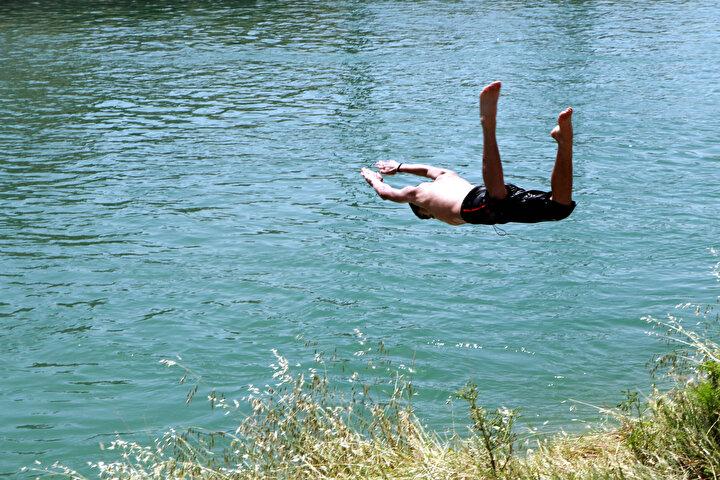 Bazı gençler de sulama kanalına indirdikleri şişme botla, bazıları da yüzerek serinlemeye çalıştı.