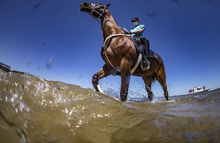 Kumsalda atlarla tur atan jandarmaların denetimlerine, bir Sahil Güvenlik botu da sahilden eşlik etti.