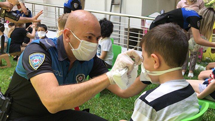 Polisler, önce çocuklara maske dağıttı ardından da ellerin 20 saniye sabun ile yıkanması gerektiğini, sokağa çıkıldığında mutlaka sosyal mesafenin korunması gerektiğini anlattı.